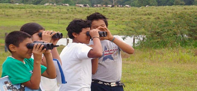 Costa Rican students try out binoculars while bird watching
